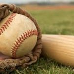 Baseball, glove and bat laying on the grass